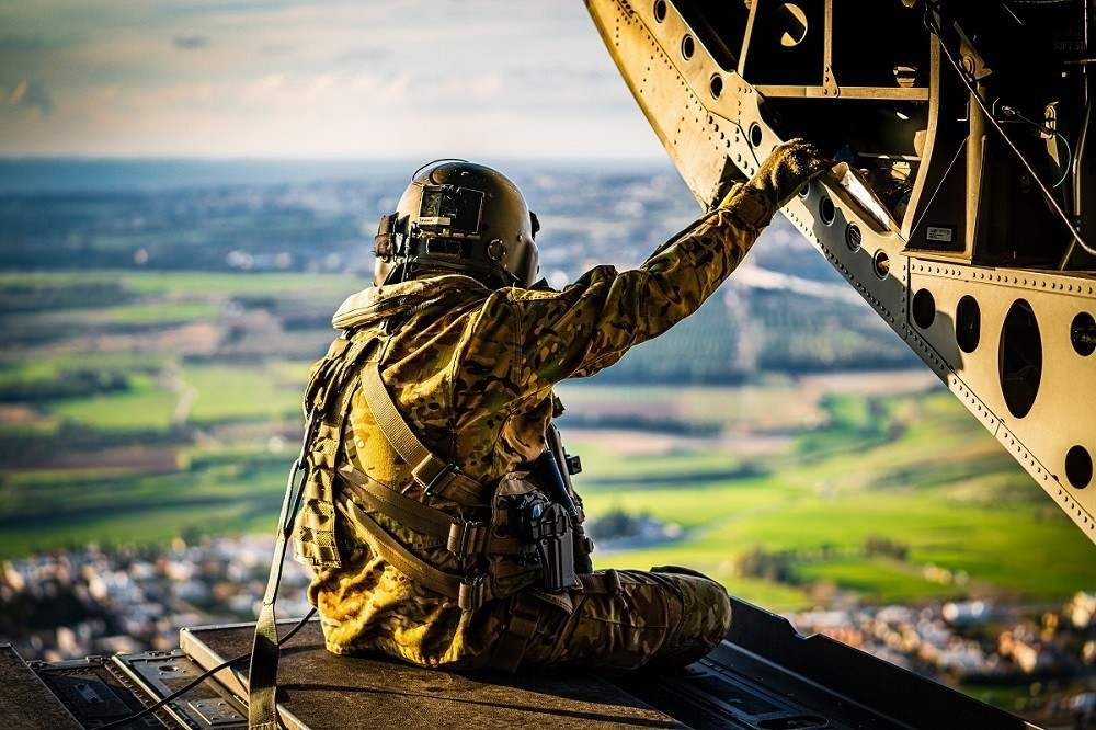 """Staff Sgt. Daniel Pennington, a flight engineer assigned to B Co """"Big Windy,"""" 1-214th General Support Aviation Battalion, takes in his 'office' view from the ramp of his CH-47 Chinook while flying over the island of Cyprus on Jan. 14, 2020."""