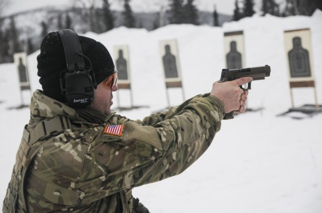 Staff Sgt. Sean E. Davis, a member of 1st Battalion, 297th Infantry Regiment, based in Joint Base Elmendorf-Richardson, Alaska, tests out the new SIG Sauer M17 Army service pistol March 1, in the Yukon Training Area on Eielson Air Force Base as part of exercise Arctic Eagle 2020.