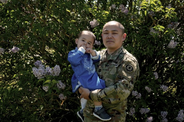 U.S. Army Capt. Vinh T. Nguyen, military police officer, assigned to the 2d Cavalry Regiment, poses with son after discussing significant aspects of  Vietnamese culture in honor of Asian American and Pacific Islander Heritage Month in Vilseck, Germany, May 18, 2020. Nguyen shared the historical background and present-day traditions of the ao dai. (U.S. Army photo by Sgt. LaShic Patterson)