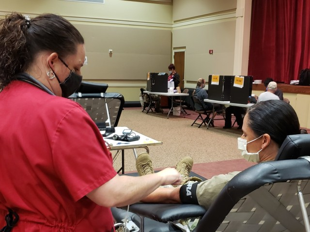 April Neely, charge phlebotomist with the American Red Cross, performs her duties during a blood donation by Capt. Monica Steadman, the chief nurse at the inpatient psychiatric services section at Winn Army Community Hospital, May 27, 2020 at the Main Post Chapel at Fort Stewart, Georgia. Neely said donating blood during the COVID-19 pandemic is safe, so long as risk mitigation procedures are followed, which include wearing a facemask, proper hand washing, and maintaining social distancing.