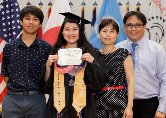 Hannah Santos, class salutatorian, poses for a photo with her family while holding her diploma during the Zama Middle High School virtual graduation June 3 at the school's auditorium. The virtual ceremony was a necessity due to the ongoing COVID-19 pandemic. (U.S. Amy photo by Kei Sasaki)