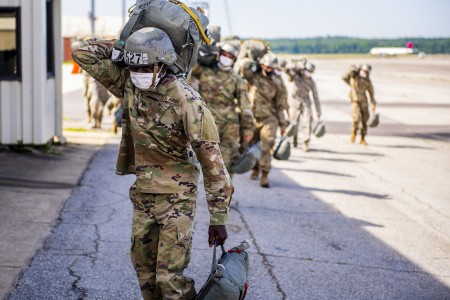 U.S. Army Airborne School students carry their primary and reserve parachutes back to the pack shed April 28, 2020 at Lawson Army Airfield, Fort Benning, Ga.
