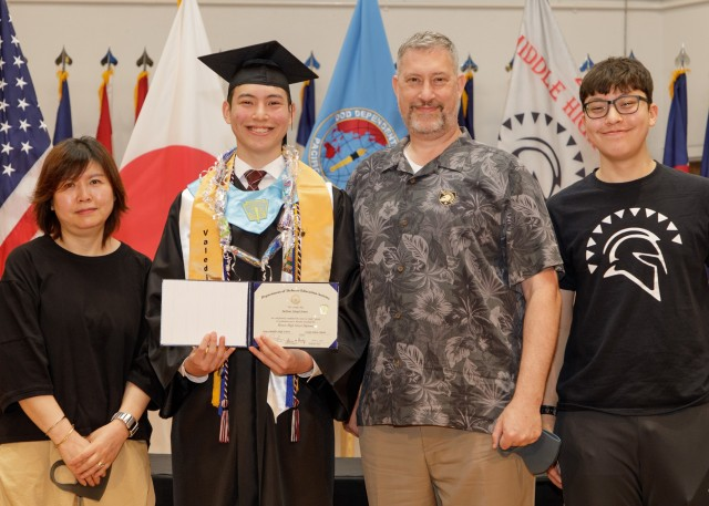 Milton Jones, class valedictorian, poses for a photo with his family while holding his diploma during the Zama Middle High School virtual graduation June 4 at the school's auditorium. The virtual ceremony was a necessity due to the ongoing COVID-19 pandemic.(US Amy photo by Kei Sasaki)
