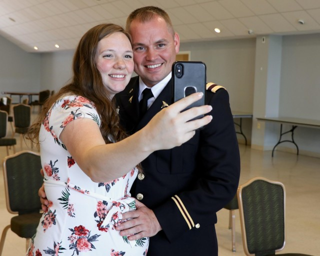 U.S. Army Physician Assistant Officer Candidate Jonathan Chamberlain, a combat medic specialist, takes a photo with his spouse before the Interservice Physician Assistant Program graduation and officer commissioning ceremony on Fort Campbell, Ky., June 5. After completing 16 months of basic medical sciences and clinical medicine courses during IPAP Phase I in San Antonio, Texas, Chamberlain and two other classmates completed 13 months of clinical rotations at Blanchfield Army Community Hospital. The Army trains about 150 Soldiers annually through IPAP, providing Soldiers an all-expense-paid path to a career in the medical field as a physician assistant and a commission for Soldiers selected from the enlisted ranks.
