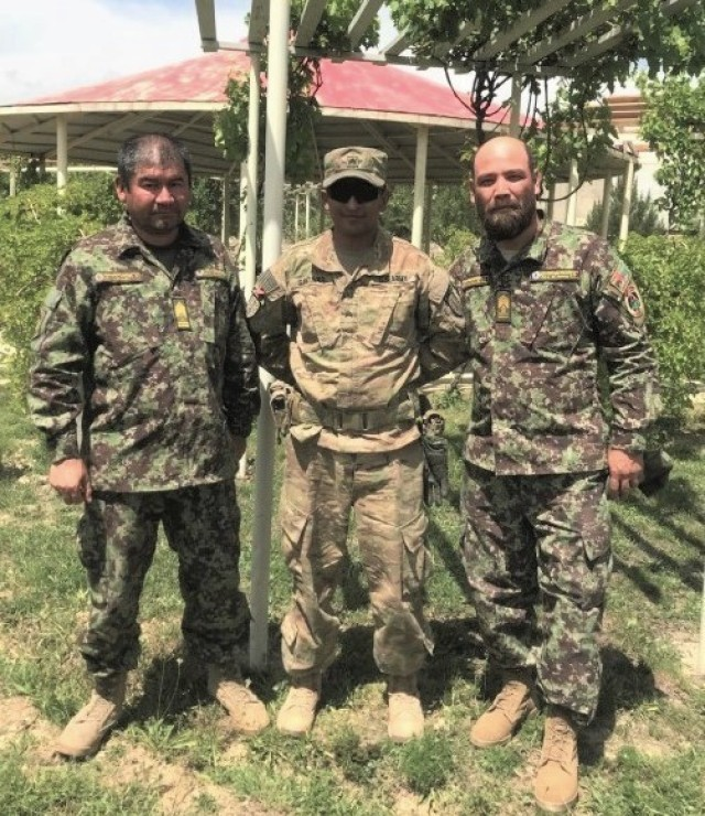 Staff Sgt. Diego Gantivar, center, a senior mechanic advisor with 3rd Squadron, 1st Security Force Assistance Brigade, poses for a photo with his Afghan partners during the brigade's deployment to Afghanistan in 2018. Gantivar is now assigned to a 45-member task force in Colombia, as part of U.S. Southern Command's enhanced counternarcotics mission.