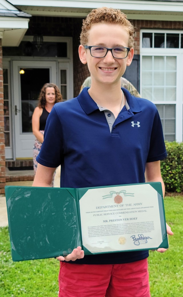 Preston Ver Hoef, the Fort Stewart Hunter Army Airfield's 2020 youth volunteer of the year award winner holds up his public service commendation medal, June 4, 2020, at his residence in Richmond Hill, Georgia. Sgt. Anthony Licata, a trumpet player assigned to the 3rd Infantry Division Band donned a Batman costume and presented Ver Hoef  the award for over 60 hours of community service through Richmond Hill Middle School by offering support to special needs students. (U.S. Army photo by Sgt. Arjenis Nunez)