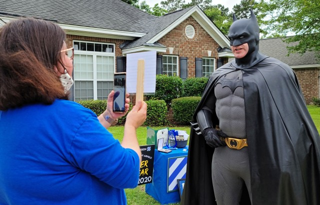 """Fort Stewart's Army Community Service support assistant Michelle Glenn, introduces Sgt. Anthony Licata, a trumpet player assigned to the 3rd Infantry Division Band who is donning a Batman costume, via a simulcast that was live-streamed for the Fort Stewart-Hunter Army Airfield communities, June 4, 2020, in Richmond Hill, Georgia. """"Batman"""" presented Preston Ver Hoef with the Fort Stewart/HAAF 2020 youth volunteer of the year award for over 60 hours of community service through Richmond Hill Middle School by offering support to special needs students. (U.S. Army photo by Sgt. Arjenis Nunez)"""