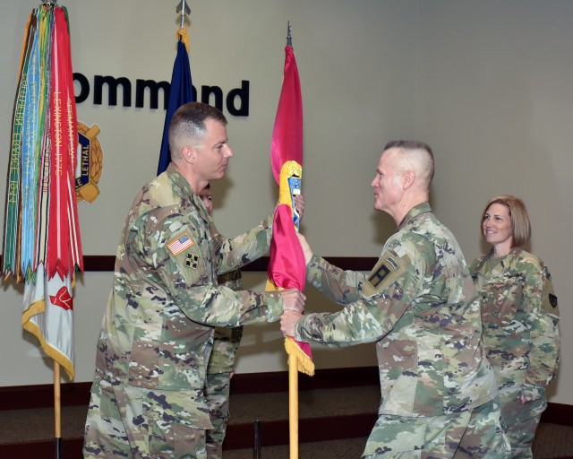 Col. Gavin J. Gardner, the new commander for the Joint Munitions Command, passes the JMC flag to Lt. Gen. Thomas S. James, Jr., while Brig. Gen. Michelle M.T. Letcher, the outgoing JMC commander looks on during a change of command ceremony held at the Rock Island Arsenal on June 11, 2020.