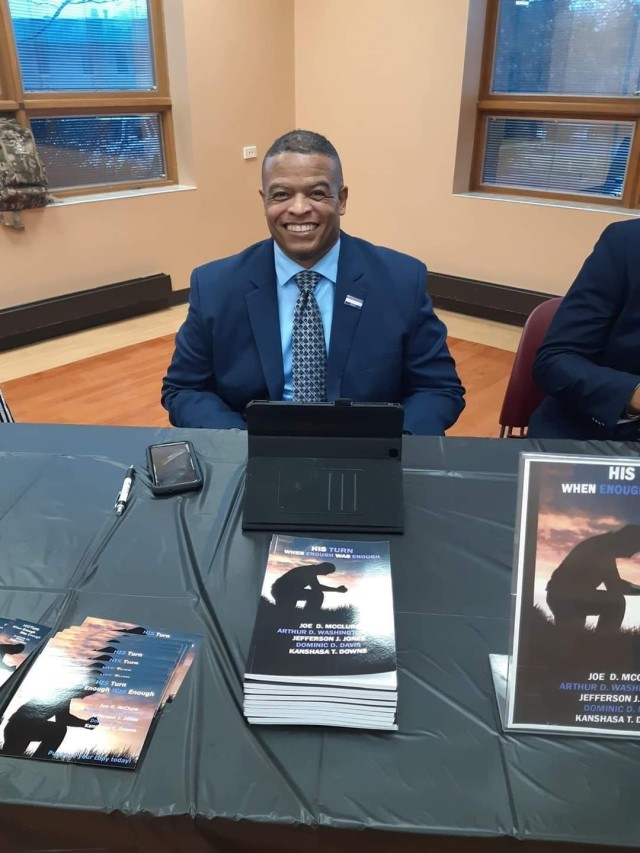 Sgt. 1st Class Arthur Washington of First Army Division West's 120th Infantry Brigade sits with copies of His Turn: When Enough was Enough during a book signing.