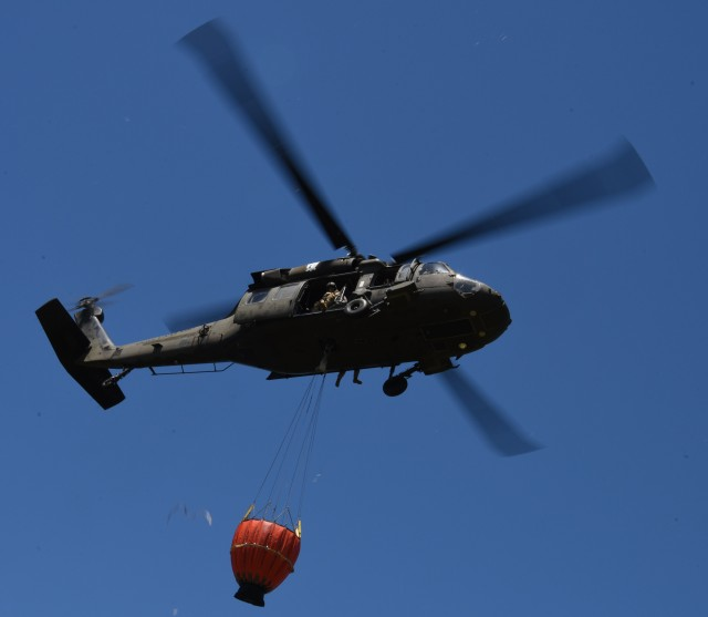 New York Army National Guard UH-60 Black Hawk helicopter crews conduct water bucket training in Riverhead, New York, June 12, 2020.  Positions are available to bring some National Guard and Army Reserve aviators back on active duty, the Army's aviation branch announced last week.