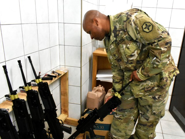 Sgt. 1st Class Curtis Ray, a food service senior non commissioned officer from Colorado Springs, Colorado is checking serial number on an air-soft M249.  Ray serves as a deputy mayor at Bemowo Piskie Training Area in Bemowo Piskie, Poland.  BPTA is a NATO base located in the eastern part of Poland.  652nd Regional Support Group, a U.S. Army Reserve Unit out of Helena, Montana, is the first U.S. Army Reserve unit tasked with providing base operations for 11 base camps in Poland.  Base support includes taking care of lodging, dining, and recreational needs of the tenant Soldiers assigned to that base.