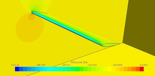 Researchers analyze a simulated air pressure field over a deformed wing inside a wind tunnel.