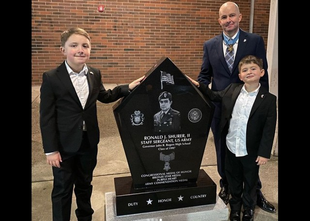 Medal Of Honor recipient Staff Sgt. Ronald Shurer II, a former 3rd Special Forces Group (Airborne) medic, shares a photo of him and two sons, Cameron and Tyler, during a ceremony at Shurer's former high school in Puyallup, Washington, Dec. 7, 2019.