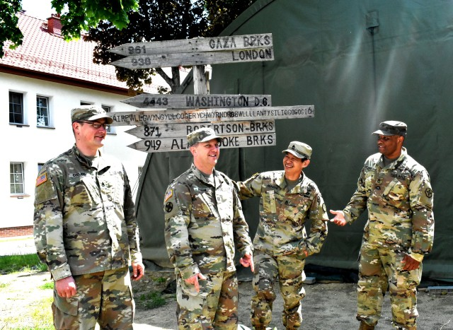 Members of mayor cell stationed in Bemowo Piskie, Poland pose by the directional sign built by Soldiers from all over the world who were stationed there in the past.  BPTA is a NATO base located in the eastern part of Poland. It is different from the other bases because it houses over 1,200 NATO forces from seven different countries.