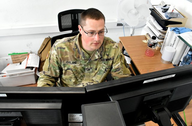 Staff Sgt. Austin Eveland, a signal support specialist from Arlington, Washington is reviewing requests for base access.  Base mayor cells streamline process for base access by organizing force protection working group with Polish security chief.  Cooperation with Polish allies builds strong Europe.