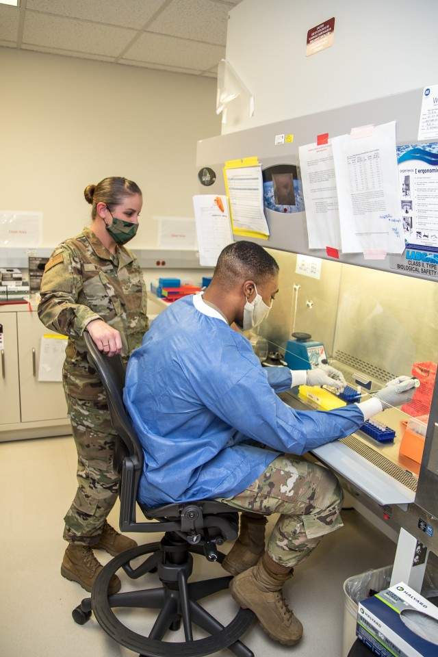 Air Force Staff Sgt. Tyler Byrd, NCOIC, Immunology, and Air Force Technical Sgt. Jennifer Weigl, NCOIC, Microbiology, prepare patient samples for COVID-19 extraction at Brooke Army Medical Center, Fort Sam Houston, Texas, June 1, 2020. BAMC laboratory technicians are completing COVID tests of all samples taken from patients at BAMC and its neighboring communities. (U.S. Army photo by Senior Master Sgt. Sarah Hanaway)