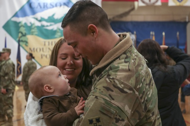 "Spc. Jacob Rhodes, assigned to 2nd General Support Aviation Battalion, 4th Combat Aviation Brigade, 4th Infantry Division, returning from an overseas deployment, is reunited with his son Henry and wife Cheyenne following a homecoming ceremony, Feb. 18, 2018, held at the William ""Bill"" Reed Special Events Center, Fort Carson, Colo. The 4CAB, 4th Inf. Div. was part of a nine-month rotation to Europe in support to Atlantic Resolve, with the mission to train with allies and partners, and demonstrate U.S. commitment to our collective security."