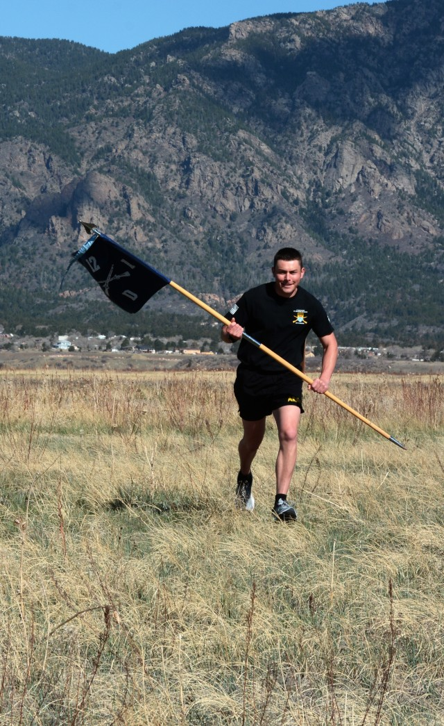 """1st Lt. Tanner Ellison, executive officer of Delta (Dog) Company, 1st Battalion, 12th Infantry Regiment, 2nd Infantry Brigade Combat Team, 4th Infantry Division, runs the """"112 for 1-12 Challenge"""" with his company guidon in memory of Pfc. Keith Williams April 28, 2020, at Fort Carson. The """"112 for 1-12 Challenge,"""" which challenged past and present Soldiers of 1st Bn., 12th Inf. Reg., to run 112 miles in the span of a month, turned into a dedication to Williams by Ellison. (Photo by Sgt. Gabrielle Weaver)"""