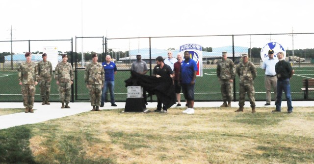 Sean McCroary, supervisory sports specialist, unveils the eighth of 10 anvil sculptures at Anvil Field June 15 as Fort Polk command and representatives from Morale, Welfare and Recreation, G3 and sports, fitness and aquatics leadership look on.