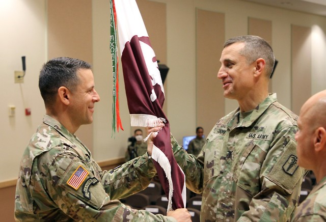 Lt. Col. Marc R. Welde, left, outgoing commander of the U.S. Army Medical Materiel Center-Korea, passes the colors to Col. Derek C. Cooper to relinquish command during a Change of Command ceremony on June 18 at Camp Carroll. Cooper served as the stand in for Col. Michael Lalor, commander of Army Medical Logistics Command, during the ceremony.