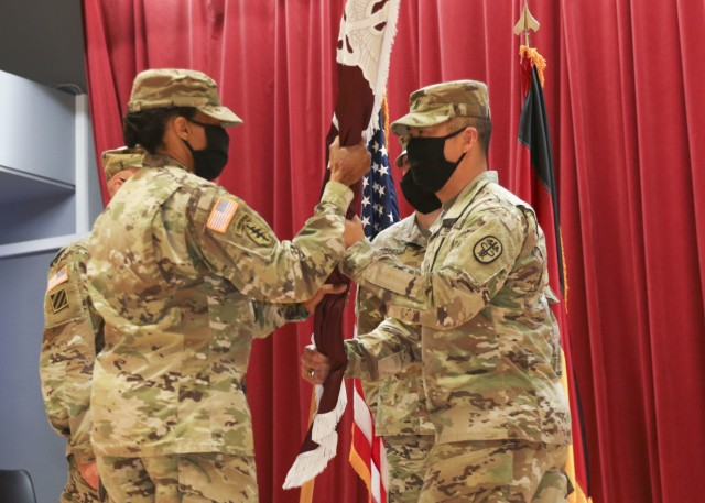 Lt. Col. Christina Buchner, commander, Troop Command, Landstuhl Regional Medical Center, receives the unit guidon from Command Sgt. Maj. Anthony Forker, during a change of responsibility ceremony, June 5.