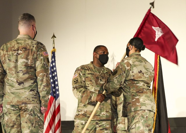 Sgt. 1st Class Timothy Johnson (center), detachment sergeant, Wiesbaden Army Health Clinic, passes the unit guidon to Col. Stacy Freeman, outgoing commander, WAHC during a change of command and responsibility ceremony, June 12.