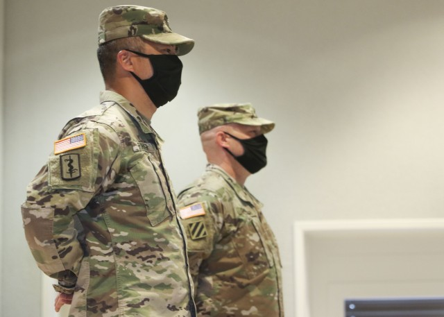 Command Sgt. Maj. Anthony Forker (left) , and Master Sgt. Richard Chandler, stand at parade rest during a change of responsibility ceremony, where Forker relinquished responsibility as LRMC's Troop Command command sergeant major to Chandler, as interim command sergeant major, June 5.
