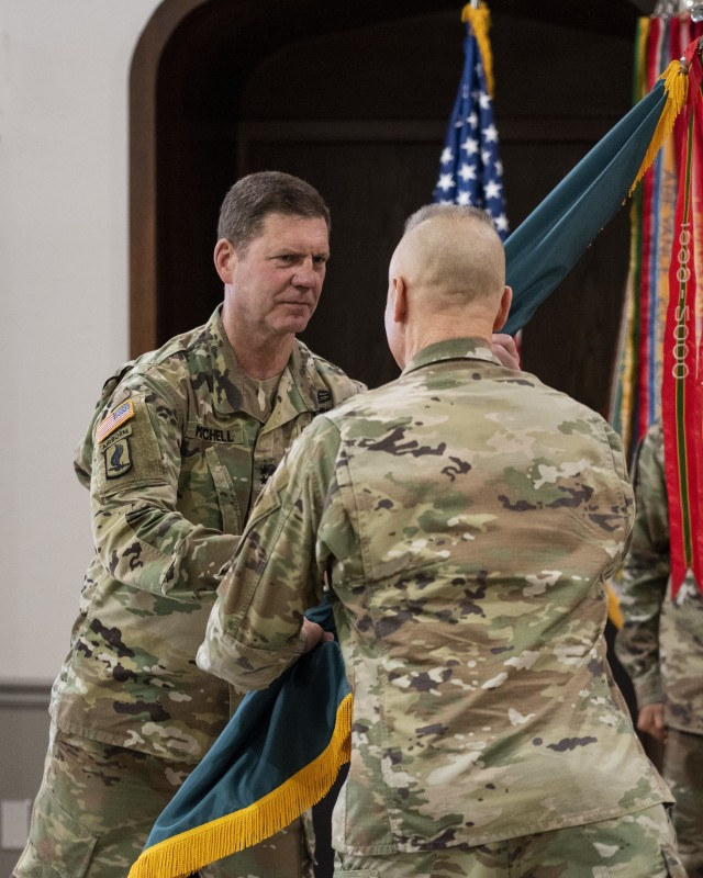 Maj. Gen. Daniel G. Mitchell, incoming commanding general of ASC, receives the flag of command from Lt. Gen. Thomas S. James, commanding general of First Army, during a change of command ceremony held June 24 at Rock Island Arsenal, Illinois.  James was acting as a proxy for Gen. Gus Perna, commanding general of the U.S. Army Command, who presided over the ceremony via live video link.