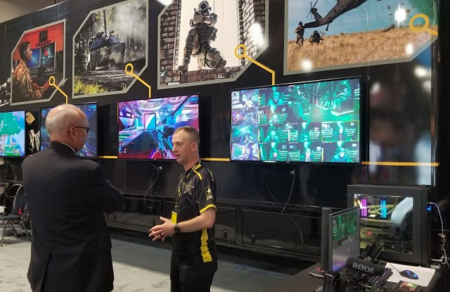 Sgt. 1st Class Christopher Jones, center, a member of the U.S. Army Recruiting Command's esports team, speaks in front of the team's semitrailer, which has gaming stations inside of it, during the Association of the U.S. Army's Annual Meeting and Exposition in Washington, D.C, Oct. 14, 2019. The command plans to create a cyber esports team and roll out autonomous recruiting operations, which will increase the mobility of recruiters with a larger social media presence.