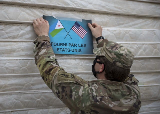 "U.S. Army Capt. Matthew Kirkpatrick, team chief, 411th Civil Affairs Battalion, Combined Joint Task Force-Horn of Africa (CJTF-HOA, posts a notice that reads, ""Provided by the United States"" prior to a ceremony at Bouffard Hospital in Djibouti City, Djibouti, June 25, 2020. CJTF-HOA donated 60 beds valued at $9,400 to the Djiboutian Ministry of Health for its efforts during the ongoing COVID-19 pandemic. (U.S. Air Force photo by Senior Airman Dylan Murakami)"