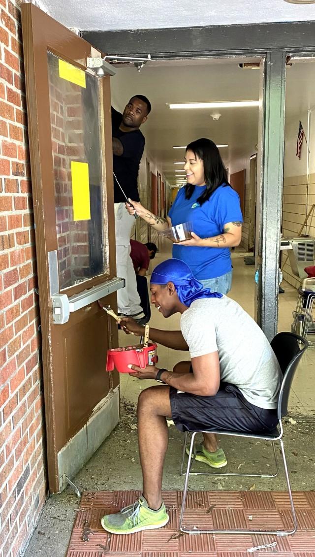 From left to right: Spc. Nalijah Caudle, Cpl. Bianca Ortiz and Spc. Elijah Johnson repaint doors at Vernon Middle School.