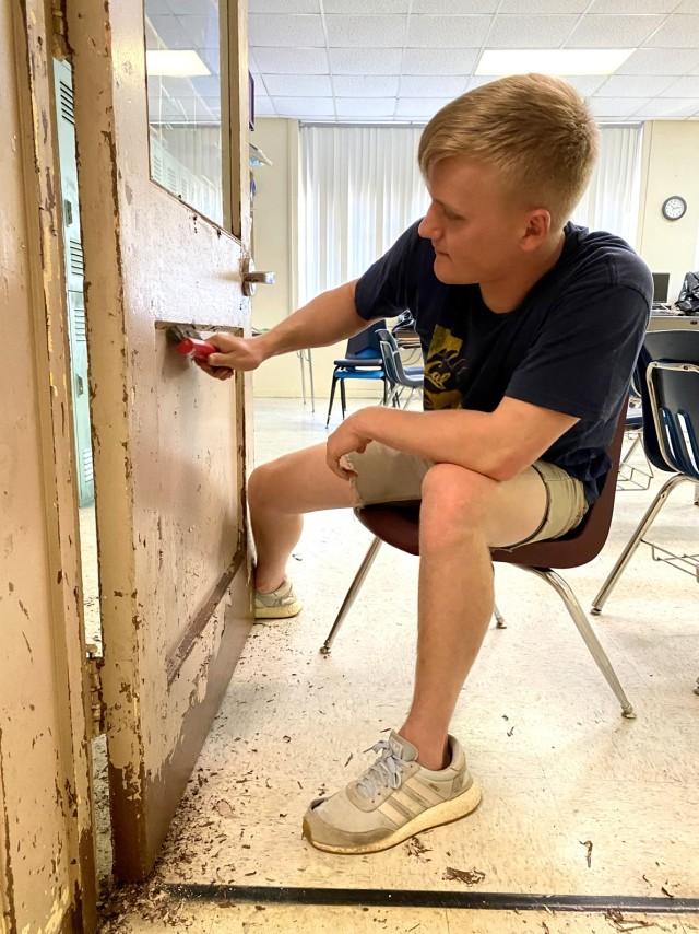 Spc. Kolton Gruber scrubs old paint off of a door.
