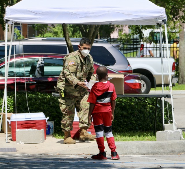 Pfc Talal Rawashdesh, a Soldier with A Company, 2-124th Infantry Battalion, hands out water to a minor outside the Lincoln Park Community Based Testing Site (CBTS) in Fort Lauderdale, Broward County. The Lincoln Park CBTS is one of two new CBTS locations in Broward County that opened recently after relocating from d. (U.S. Army National Guard photo by Maj. Jesse Manzano.)
