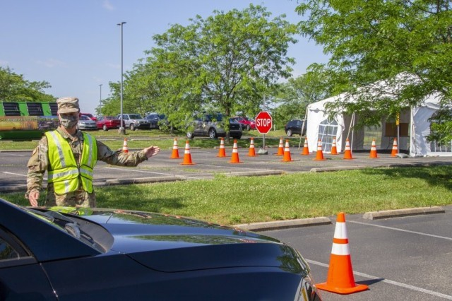 Pfc. Isaiah Gibson, geospatial engineer assigned to Headquarters and Headquarters Company, 63rd Theater Aviation Brigade, directs traffic at a COVID-19 testing facility in Shelbyville, Ky., June 24, 2020. (U.S. Army National Guard photo by 1st. Lt. Cody Stagner/Released)