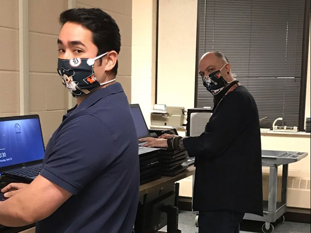 Billy Breeden (left) and Christian Gierak (right), Tank-automotive and Armaments Command Desktop Support-G6, practice social distancing and the wear of cloth face coverings while working on laptops at the Detroit Arsenal.  The Centers for Disease Control and Prevention has determined that wearing cloth face coverings helps slow the spread of the Coronavirus Disease 2019.