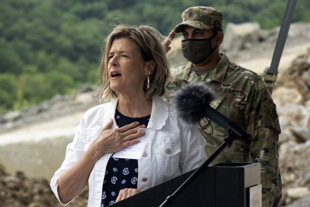 Tennessee District 40 Rep. Terri Lynn Weaver sings the National Anthem at the Center Hill Lake Auxiliary Dam July 1, 2020 during a ceremony celebrating the completion of the last phase of repairs for the $353 million Center Hill Dam Safety Rehabilitation Project. The U.S. Army Corps of Engineers Nashville District recently finished constructing a roller compacted concrete berm to reinforce the auxiliary dam at Center Hill Lake, a secondary earthen embankment that fills a low area in the landscape just east of the main dam. (USACE Photo by Leon Roberts)