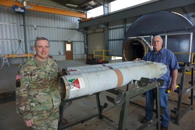 LEMC Commander LTC Dennis Williams and LEMC employee Chuck Grove with the 500th successful rocket motor processed through LEMC's ARMD facility.