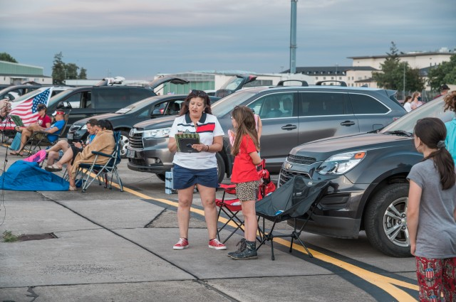 WIESBADEN, Germany - Jane Porto-Turner, advertising and sponsorship manager for MWR, conducts a trivia contest with a young spectator July 4, 2020, at Wiesbaden Army Airfield. MWR hosted a live feed of the event.