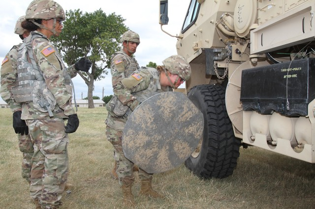 Pvt. Meagan Brewer, an Army National Guard Soldier from Grove, Oklahoma, hefts an outrigger sand pad, a roughly 30-pound bulky metal disc, back onto the TPQ-53 radar. Brewer wanted to become an 11B Infantry Soldier but instead found an MOS she likes in field artillery.
