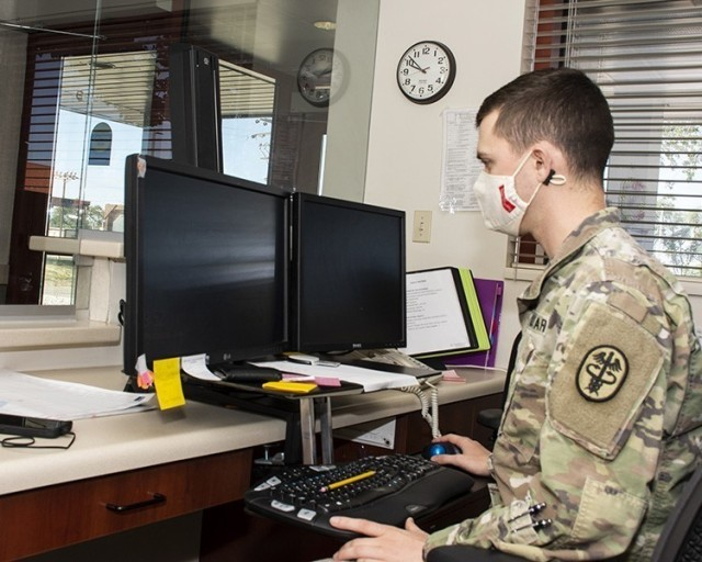 Spc. Nathan Baker, a medical lab technician, does some of the duties that a civilian did at the entry to Dugway Occupational Health Clinic. He answers the phone, keeps personnel from using the front door (entry is temporarily moved to the side) and takes package deliveries.