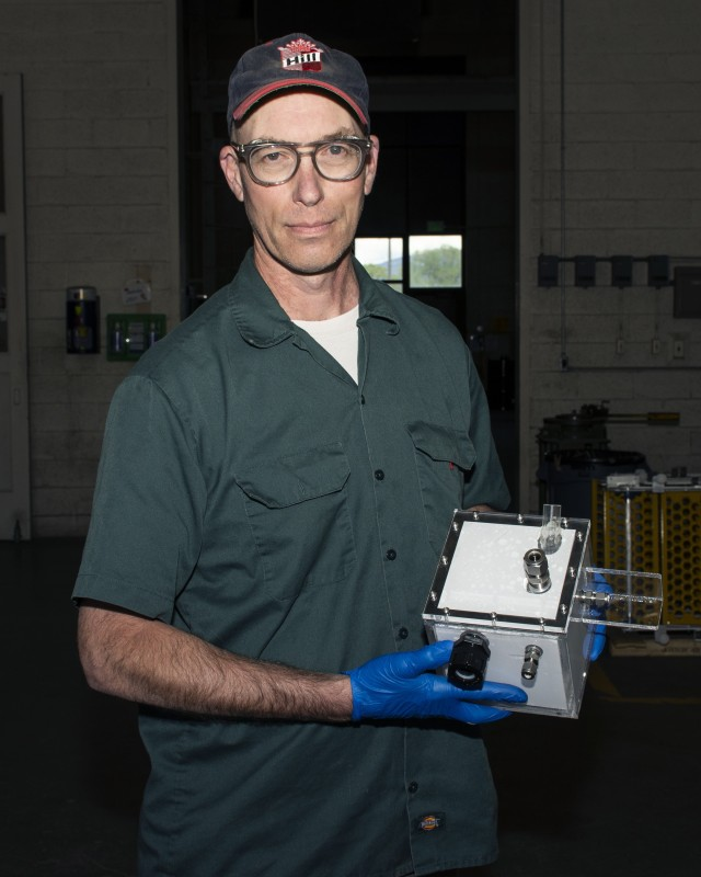 Sam Hill, Supervisor of the Metal Shop, holds a Secondary Containment Box his shop crafted largely from acrylic. A computerized laser cutter made each panel so perfectly that smoothing or final fitting were not necessary. The box will contain a sensor to count the number and size of chemical vapor droplets passing through -- important data when you're testing chemical agent detectors. Photo by Al Vogel, Dugway Public Affairs