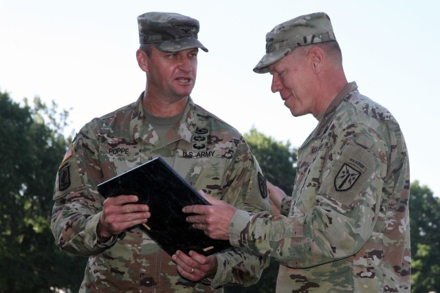 Maj. Gen. Kenneth Kamper, Fires Center of Excellence and Fort Sill commanding general, hands the Army Capabilities Manager charter to Col. Carl Poppe during a change of charter ceremony July 2, 2020, at the Old Post Quadrangle. Poppe was most recently the Directorate of Training Development and Doctrine director.