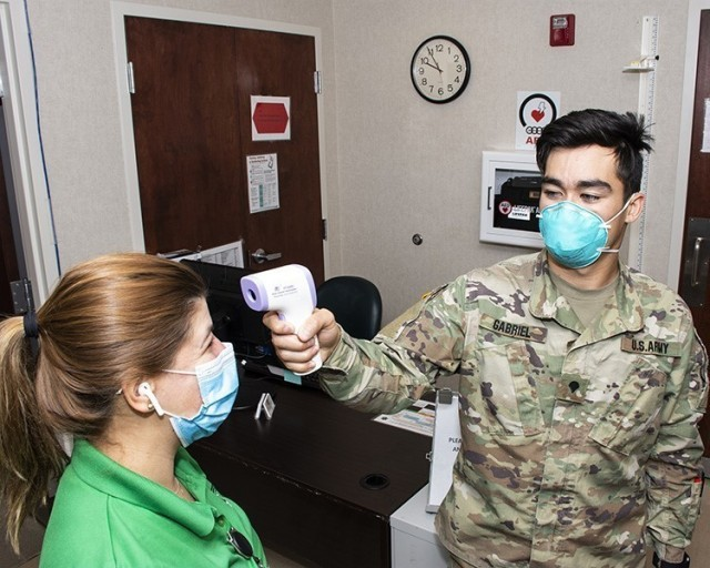 Patricia Vice has her temperature taken by Spc. Reef Gabriel upon entering the Dugway Occupational Health Clinic. As much as possible, the services provided by separate rooms have been combined into a few rooms, to limit the travel of visitors within the clinic.