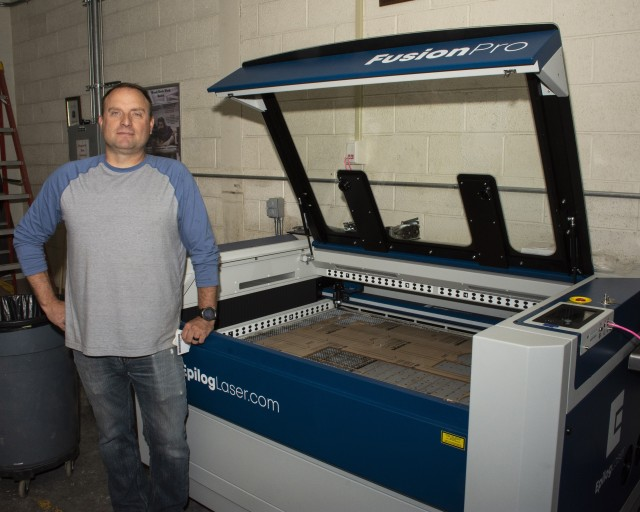 Jody Nielson, engineer technician with Dugway Proving Ground's Metal Shop, stands beside a computerized laser cutter used for cutting acrylic sheets. It cuts to exacting dimensions, and the pieces require no smoothing or final finishing. The laser cutter saves a lot of labor, time and expense. Photo by Al Vogel, Dugway Public Affairs