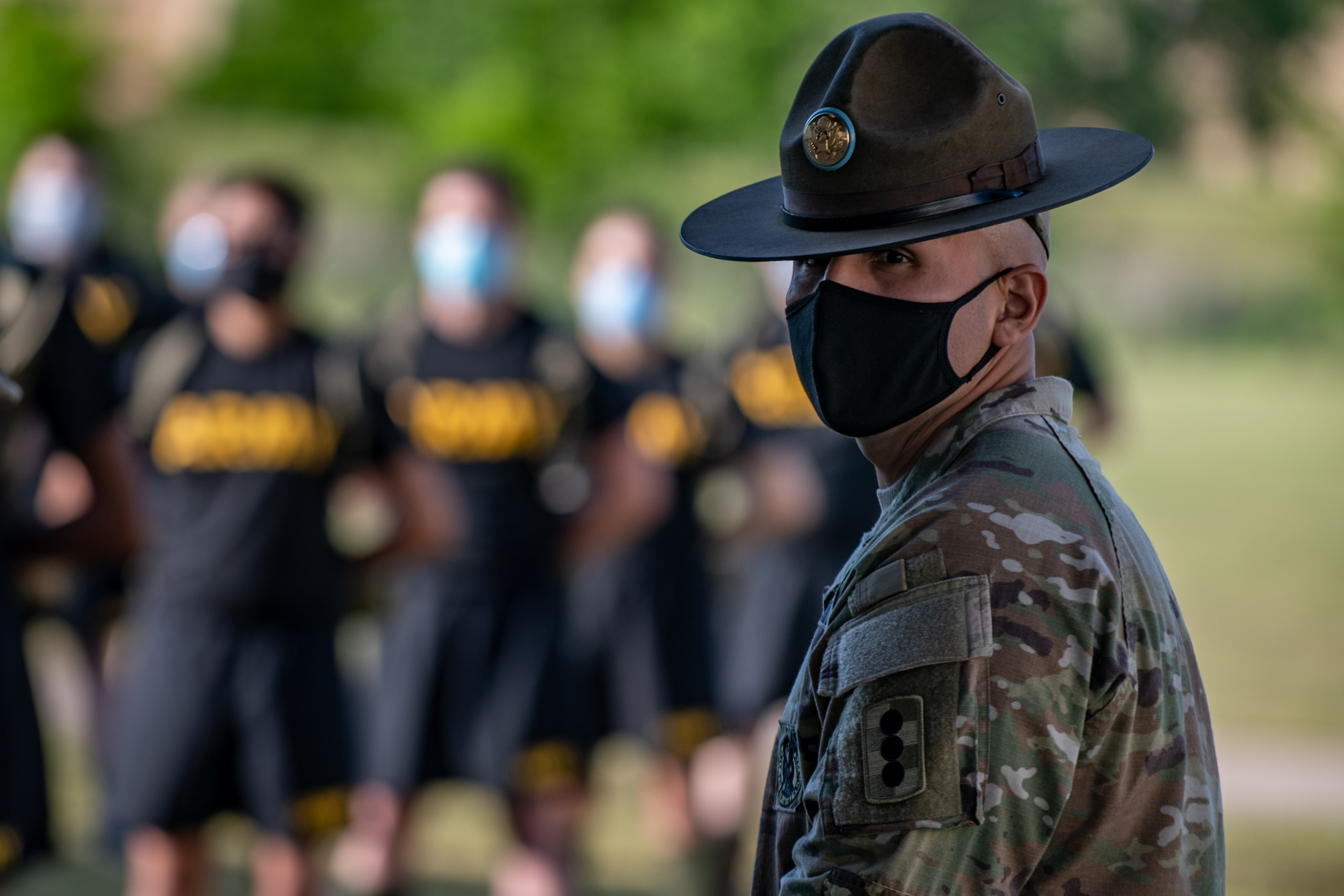 A drill sergeant watches over trainees as they stand in formation while wearing masks and maintaining physical distancing during reception before entering basic combat training May 14, 2020, Fort Sill, Okla.