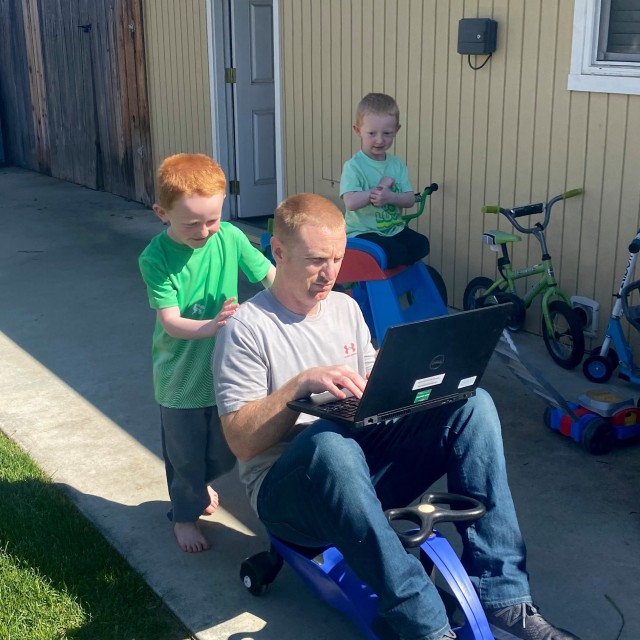 Fort Hunter Liggett HHC 1st Sgt. Aaron Halter shows off his multi-tasking skills by teleworking and having family time, while his wife, who is a nurse, continues her critical function to support the community. Courtesy photo.