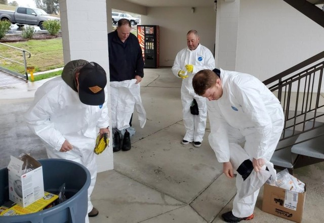 The Fort Hunter Liggett Team Clean consists of trained emergency services staff wearing protective gear to disinfect areas as needed. Once a report of someone who may have COVID-19 exposure or exhibits symptoms, this team researches all locations and individuals the person came into contact with. Team Clean then disinfects all identified areas. Proper wearing and disposal of protective gear is crucial to avoid spread of the COVID-19 virus. Courtesy photo.