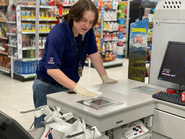 Post facilities that remain open to service customers disinfect high-contact surfaces several times a day, enforce social distancing and limit amount of customers in building at one time. Pictured is Fort Hunter Liggett PX employee Kaleb Derbonne cleaning his register area. Courtesy photo.