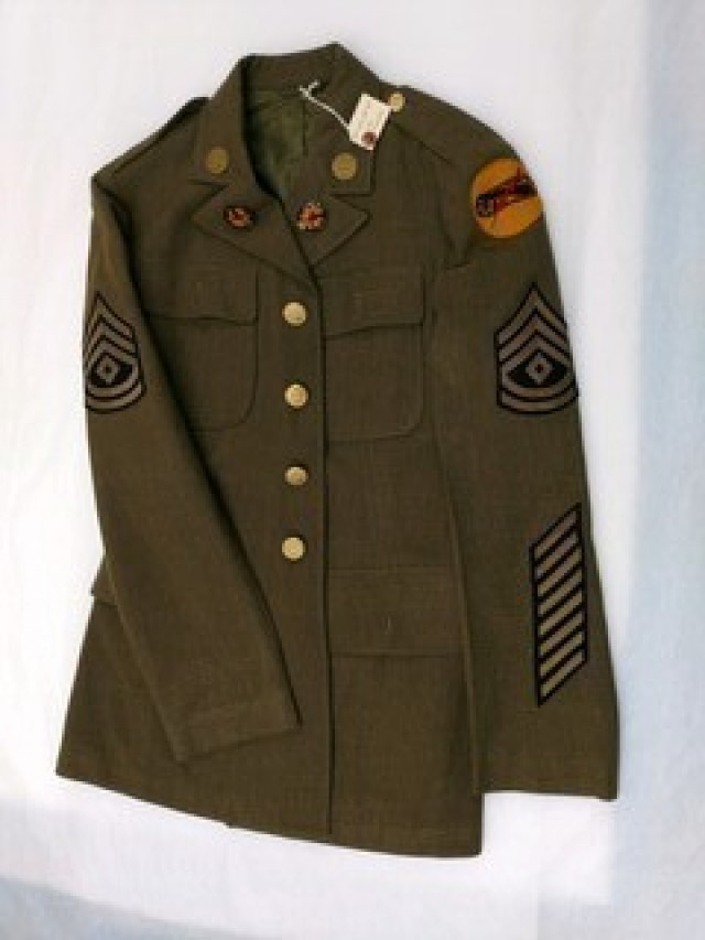 Fort Bliss, Texas - 1933: 7th Cavalry Brigade (Mechanized) Patch Uniform with 7th Cavalry Brigade Patch worn by 1SG William D. Elder, B Troop, 1st Cavalry Regiment, 7th Cavalry Brigade at Fort Bliss, 1938. When the new armored unit needed a shoulder patch, Maj. Gen. Robert W. Grow, then a Major and Brigade Adjutant, held a design contest. Col. George Linthwaite, then a newly enlisted Private, won with his design, which was then designated as the official 7th Cavalry Brigade (Mechanized) insignia. It was a circular patch four inches in diameter, with a solid yellow-gold background to symbolize the Cavalry heritage. A stylized black tank track with a drive and idler sprockets symbolized mobility and armor protection. A single black cannon barrel symbolized firepower. A red lightning bolt symbolized the striking power (shock effect) of the new armored force. Part of the 1st Armored Division & Fort Bliss Museum collection. (Image courtesy of the 1st Armored Division & Fort Bliss Museum)