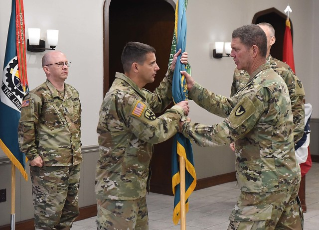 Col. Michael Clark, incoming commander, LOGCAP Support Brigade, receives the unit colors during a change of command ceremony July 10 in Heritage Hall, Rock Island Arsenal, Illinois. (Photo by Jon Micheal Connor, ASC Public Affairs)